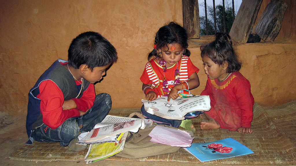 Three children read a book while pointing at the pictures.