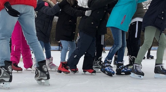 Throng of feet of ice skating people